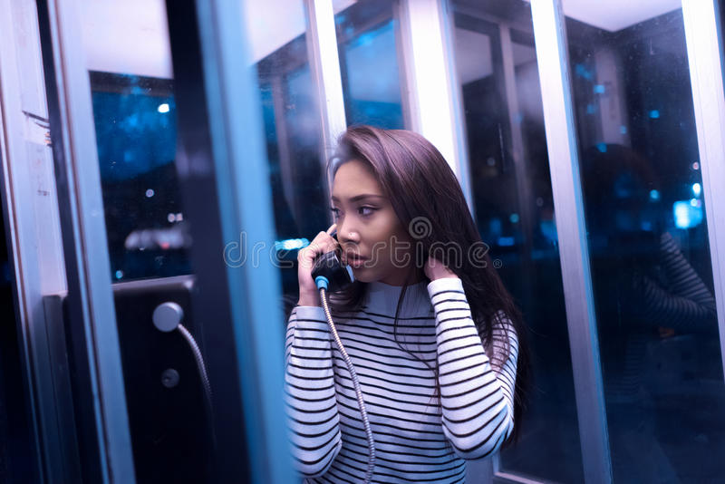 Woman In White And Black Stripe Long Sleeve Shirt Using Telephone Inside Telephone Booth During Night Time Free Public Domain Cc0 Image
