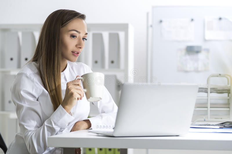 Download Woman In A White Blouse With Coffee And Laptop Stock Photo - Image: 83722147