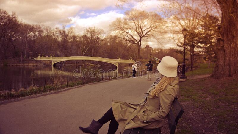 Woman in White Bucket Hat, Brown Coat and Boots Sitting on Bench at Park royalty free stock photo
