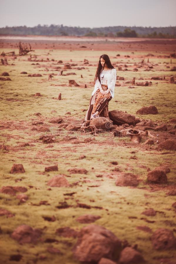 Woman in White Cardigan and Brown Pants Sitting on Stump during Daytime royalty free stock image