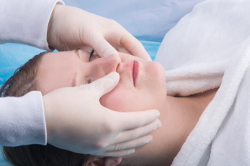 Woman, in a white coat, doing facial massage at Spa treatments, close-up stock image