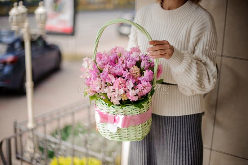 Woman in white cute sweater holding a beautiful green wicker basket with pink flowers stock photo