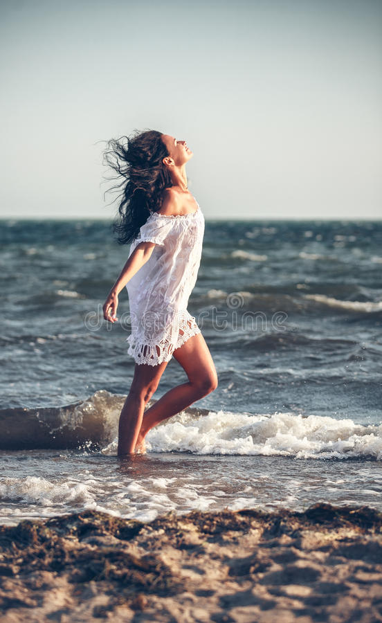 Woman in a white dress on the beach stock photo