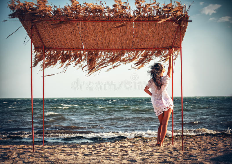 Woman in a white dress on the beach. Young woman in a white dress on the beach royalty free stock photography