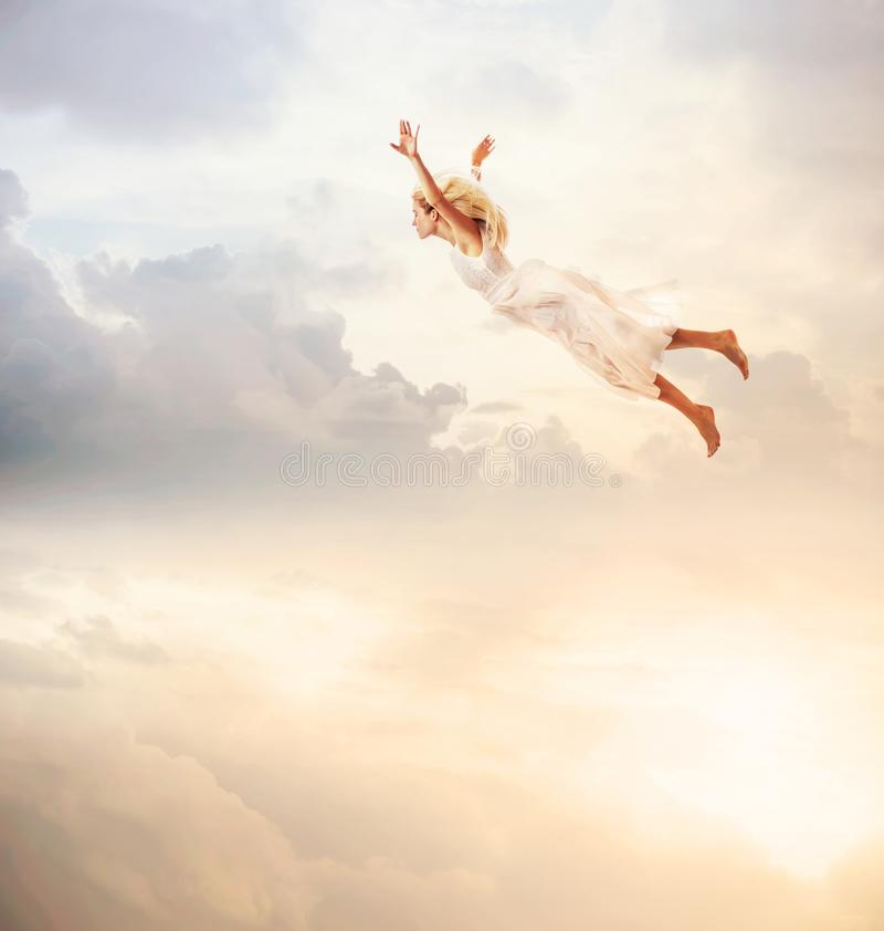 Woman in a white dress flying in the sky. Serenity stock photography