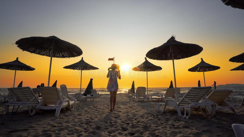 Woman in white dress at sunset on tropical beach. Woman in white dress and hat walk toward camera on beach in the seaside resort with sun loungers and wooden royalty free stock images