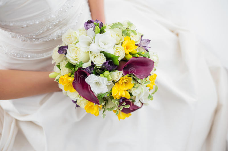 Woman in a white dress holding her wedding flowers. Woman in a white dress holding her beautiful wedding flowers stock images
