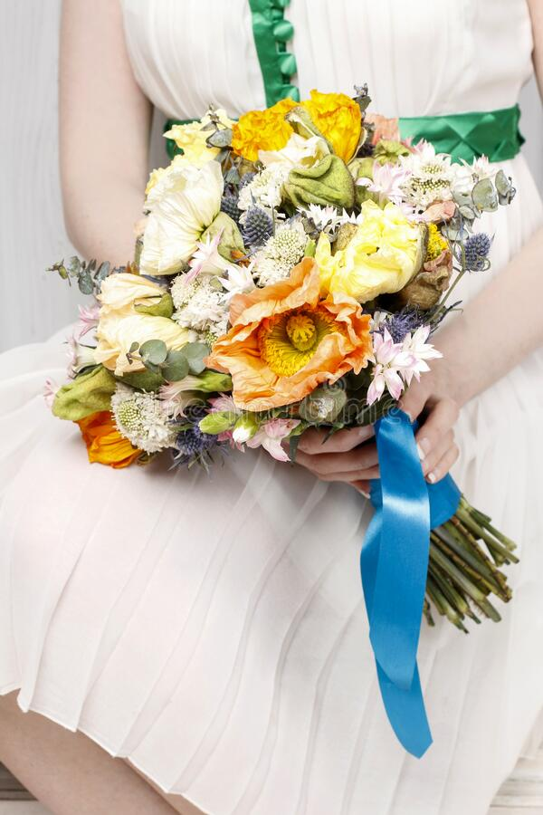 Woman in white dress holding a wedding bouquet of poppies and carnations. Party time royalty free stock images