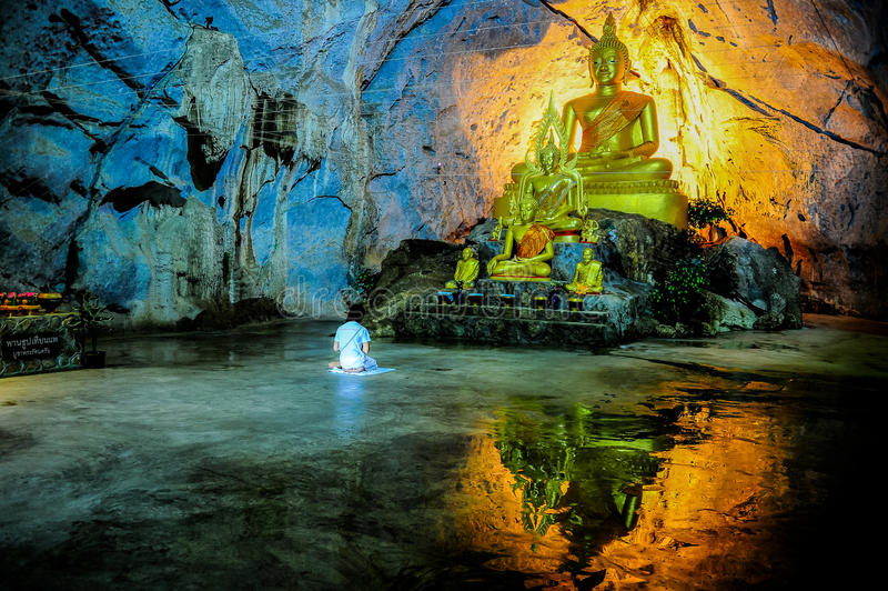 Woman in white dress meditating in fron of Buddha image. Saraburi, Thailand - June 2, 2012 : Woman in white dress meditating in fron of Buddha image in the cave royalty free stock images