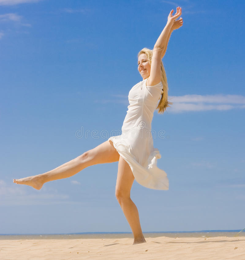 Woman in white dress practising yoga stock images