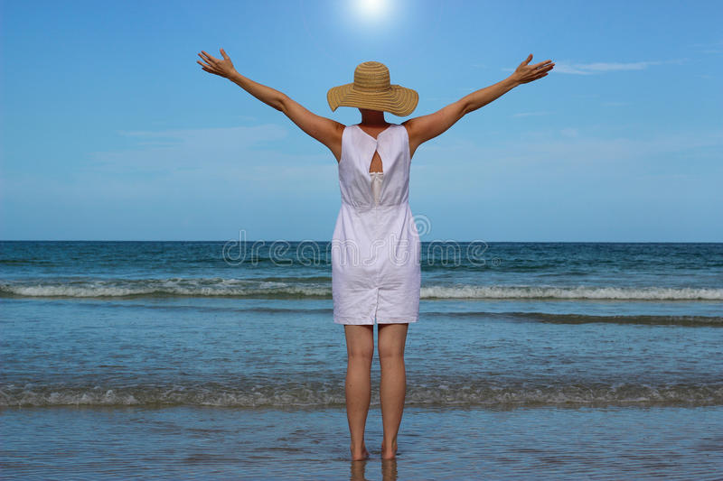 Woman In White Dress Raising Arms Looking At Ocean stock images
