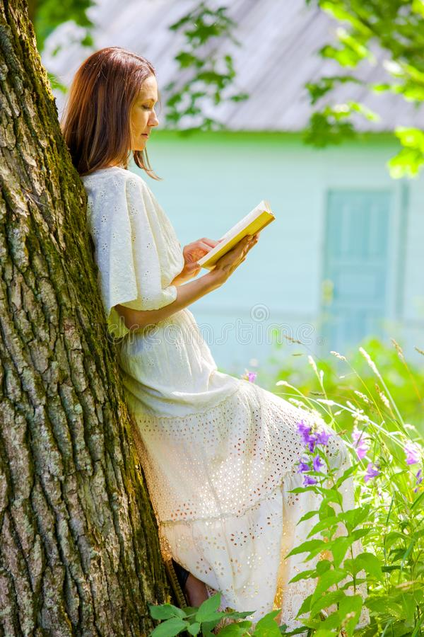 Beautiful woman in white dress reads a book stock photography