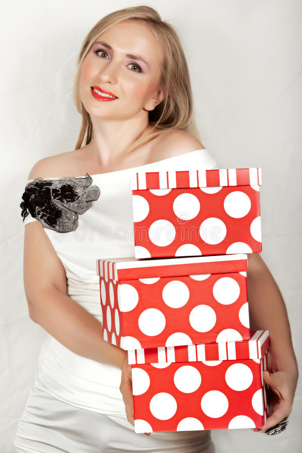 Woman in white dress and red boxes. royalty free stock photography