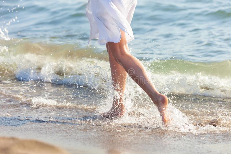 Woman in white dress run through the water on sandy sea beach sunny summer day lower body royalty free stock images