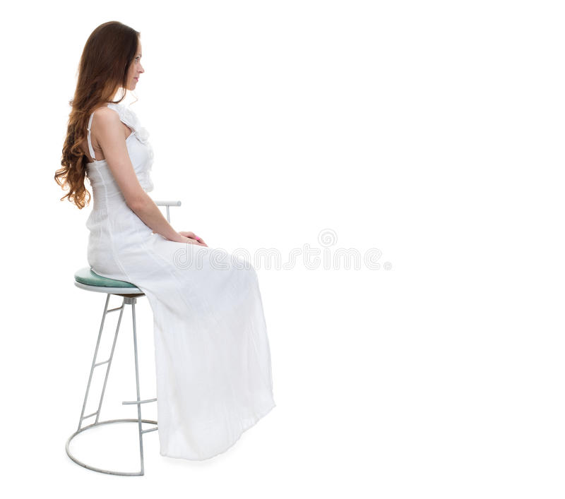 Woman with white dress sitting on chair in studio stock photography