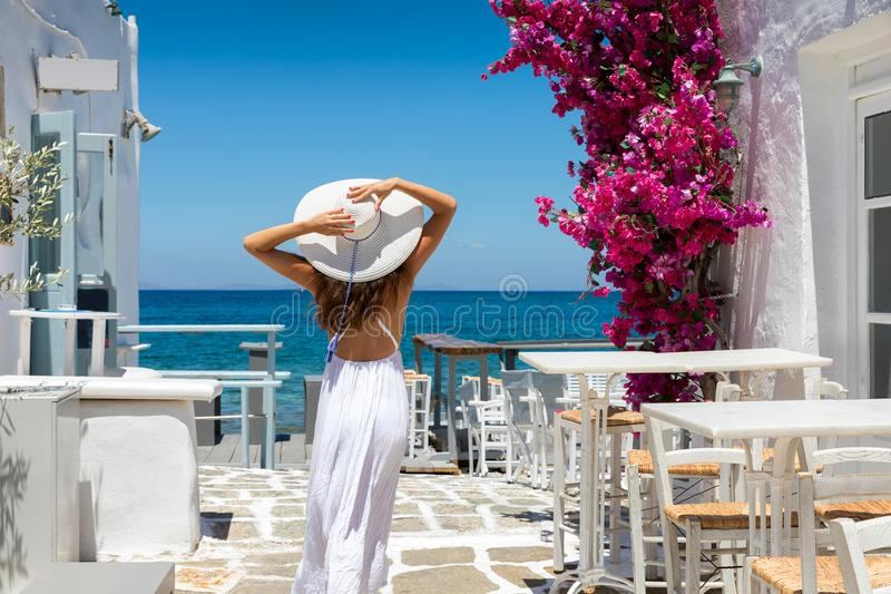Woman in white dress stands in a typical whitewashed alley on a Greek island in the cyclades, Paros royalty free stock image