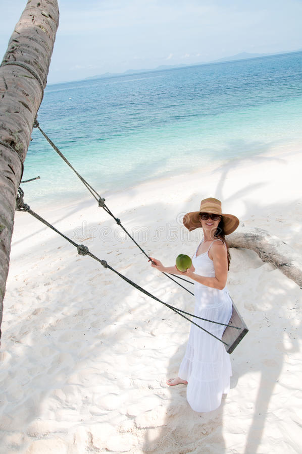 Woman in white dress swinging at tropical beach royalty free stock photography