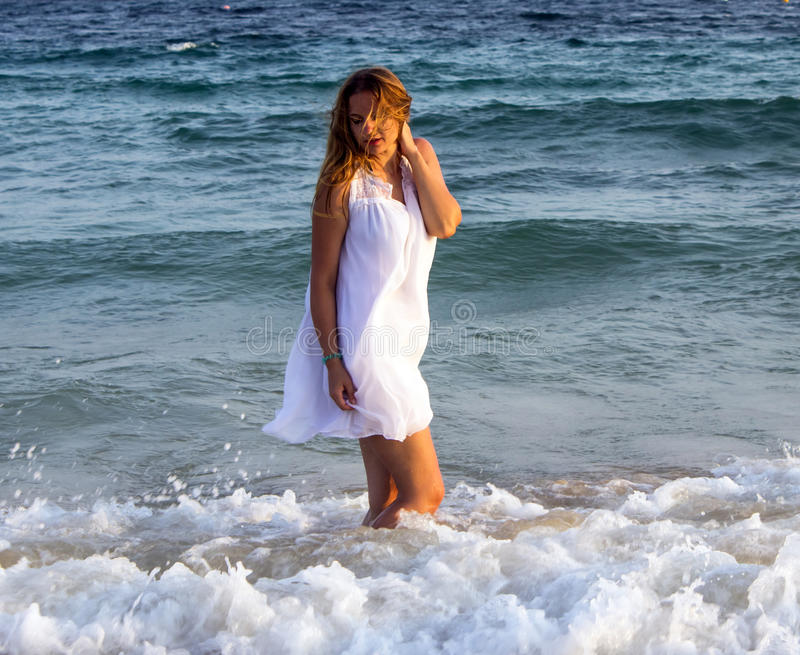 Woman in an white dress walking on the beach. royalty free stock image