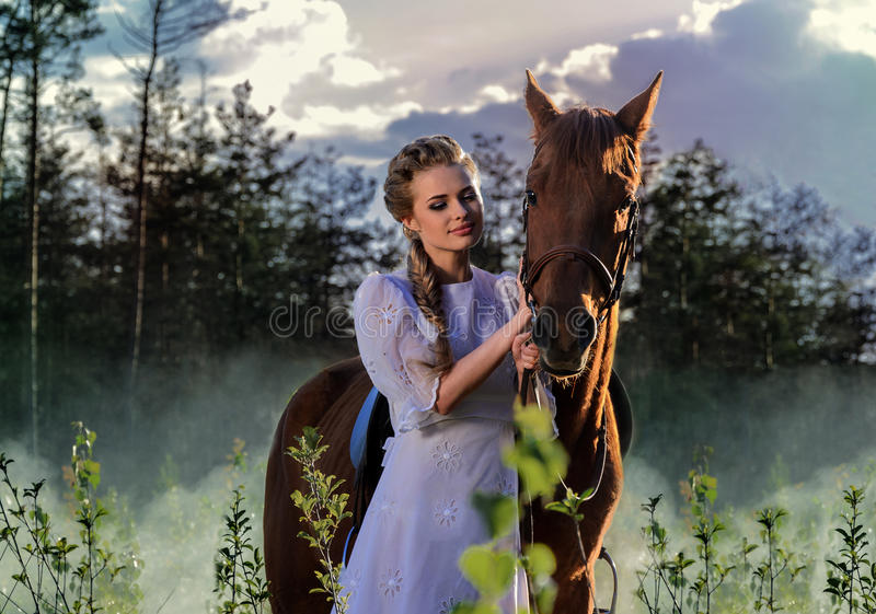 Woman in white dress walking with horse in green countryside stock image
