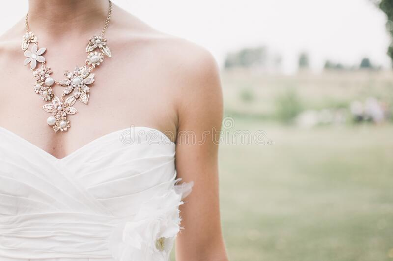 Woman in White Dress Wearing Gold Chunky Necklace during Daytime royalty free stock image