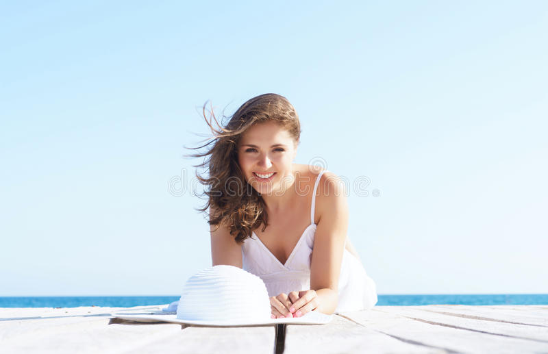 Woman in a white dress on a wooden pier royalty free stock photography