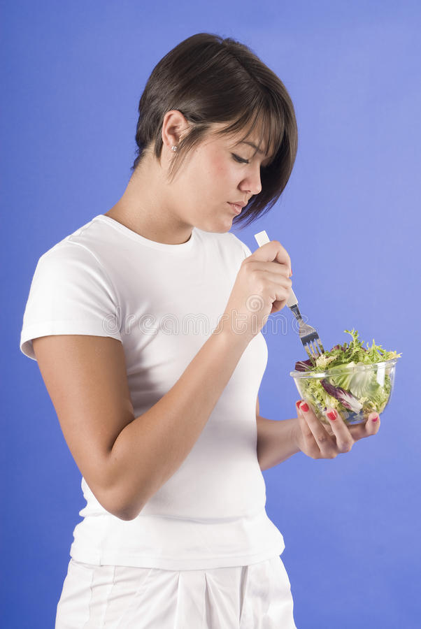 Woman in white eating a vegetable salad stock photos