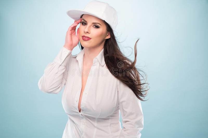 Woman in White Fashion with Cap Showing Cleavage. Half Body Shot of a Pretty Long Hair Woman, Posing in White Fashion with Cap, Showing Cleavage While Looking at royalty free stock photo