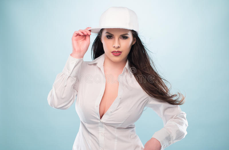 Woman in White Fashion with Cap Showing Cleavage. Half Body Shot of a Pretty Long Hair Woman, Posing in White Fashion with Cap, Showing Cleavage While Looking at stock image