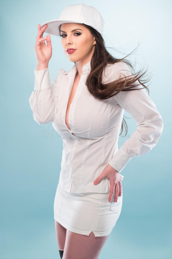 Woman in White Fashion with Cap Showing Cleavage. Half Body Shot of a Pretty Long Hair Woman, Posing in White Fashion with Cap, Showing Cleavage While Looking at stock photography