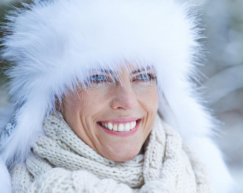 Woman with white fur cap in winter. Smiling woman with white fur cap in winter snow royalty free stock photos