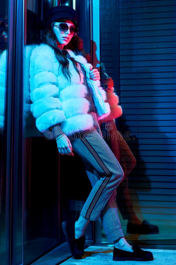 Woman in white fur coat standing with her back leaning on glass stock images