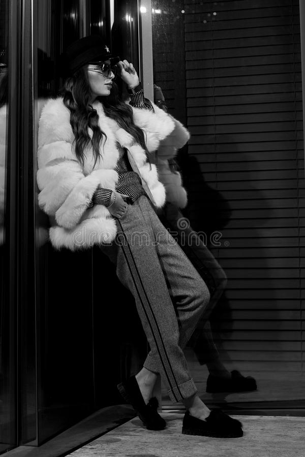 Woman in white fur coat standing with her back leaning on glass royalty free stock photo