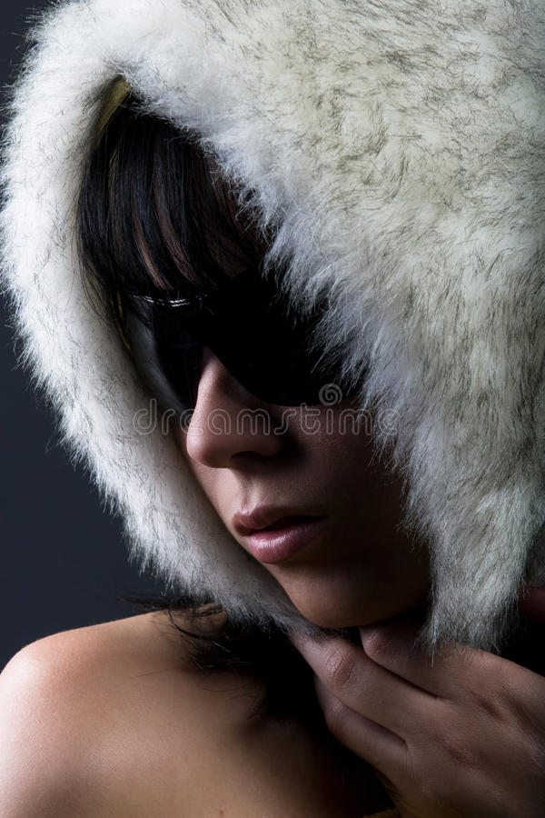Woman in white fur hat. Portrait of young woman with bare shoulders in sunglasses and white furry hat, studio background stock photography