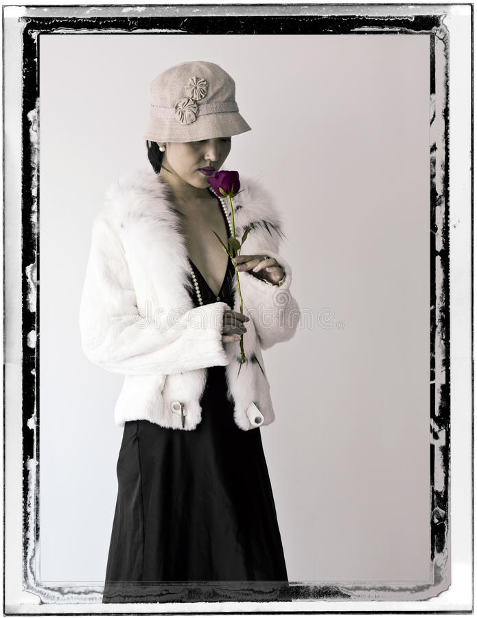 Woman in White Fur with Rose. A woman dressed in 1920's fashion smells a rose in an antiqued photo stock photo