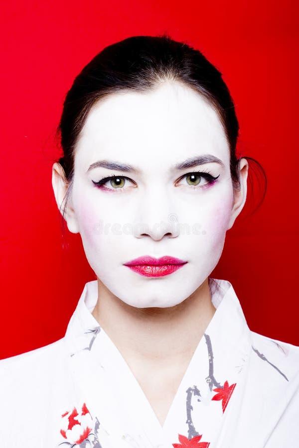 Woman in white geisha makeup stock photo