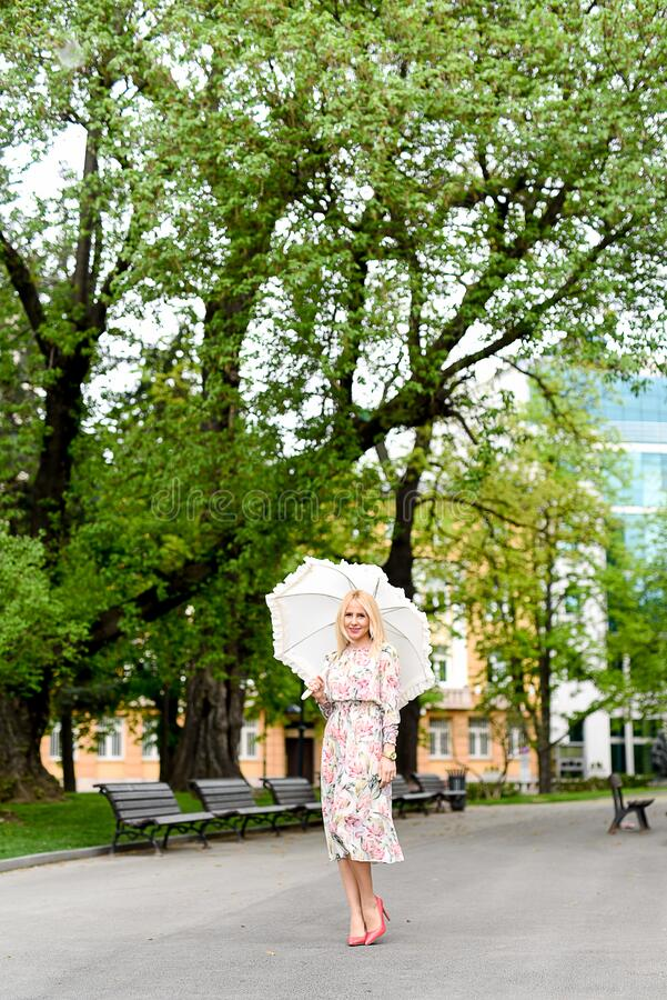 Woman in White Green and Red Floral Holding White Umbrella on Gray Concrete Pathway Near Brown Wooden Bench Near Trees during Dayt stock photos