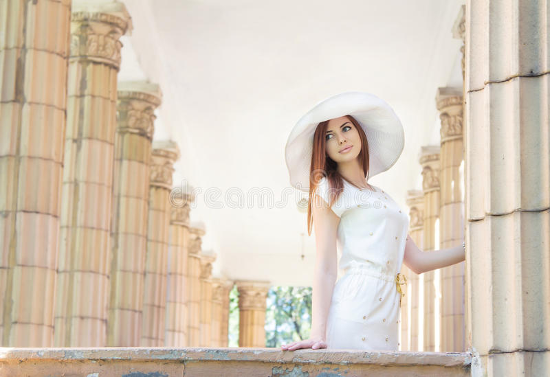 Woman in white hat between columns stock photos