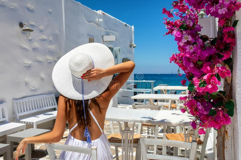 Woman sits in a bar on a classic, Greek setting in Greece, Cyclades islands stock photography