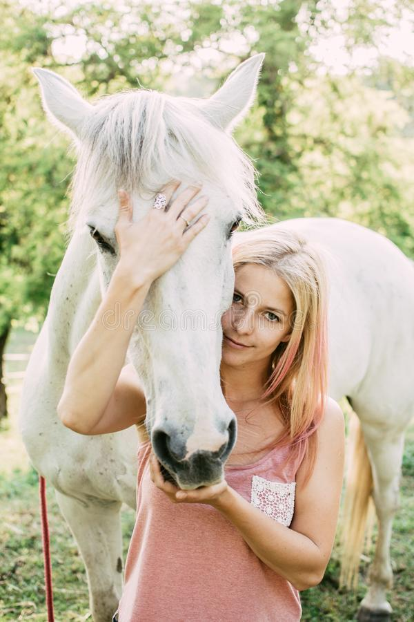 Woman with white horse outdoor. stock photos