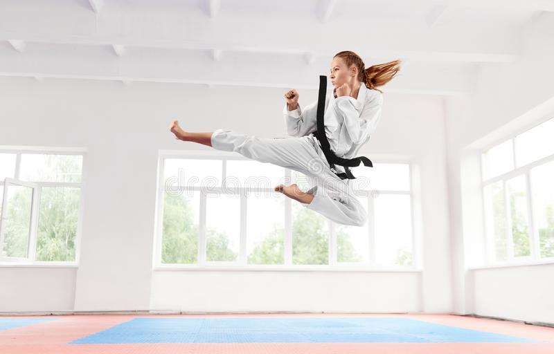 Woman in white kimono with black belt jumping and performing kick. royalty free stock photos