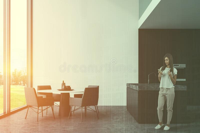 Woman in white kitchen with island and table royalty free stock photos