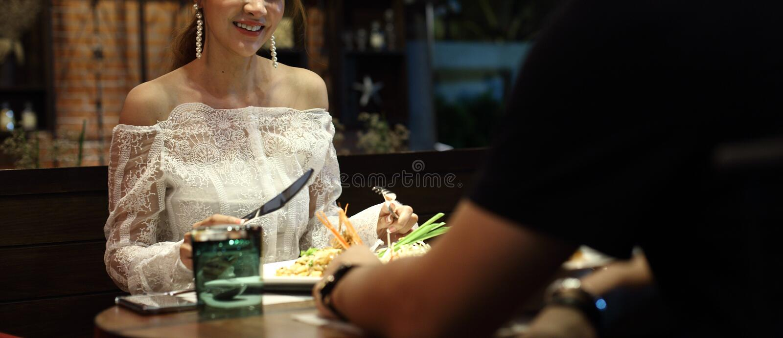 Woman white lace dress have dinner in restaurant. With low light candle waiting for lover to join celebrate anniversary night together but come so late and feel stock photo