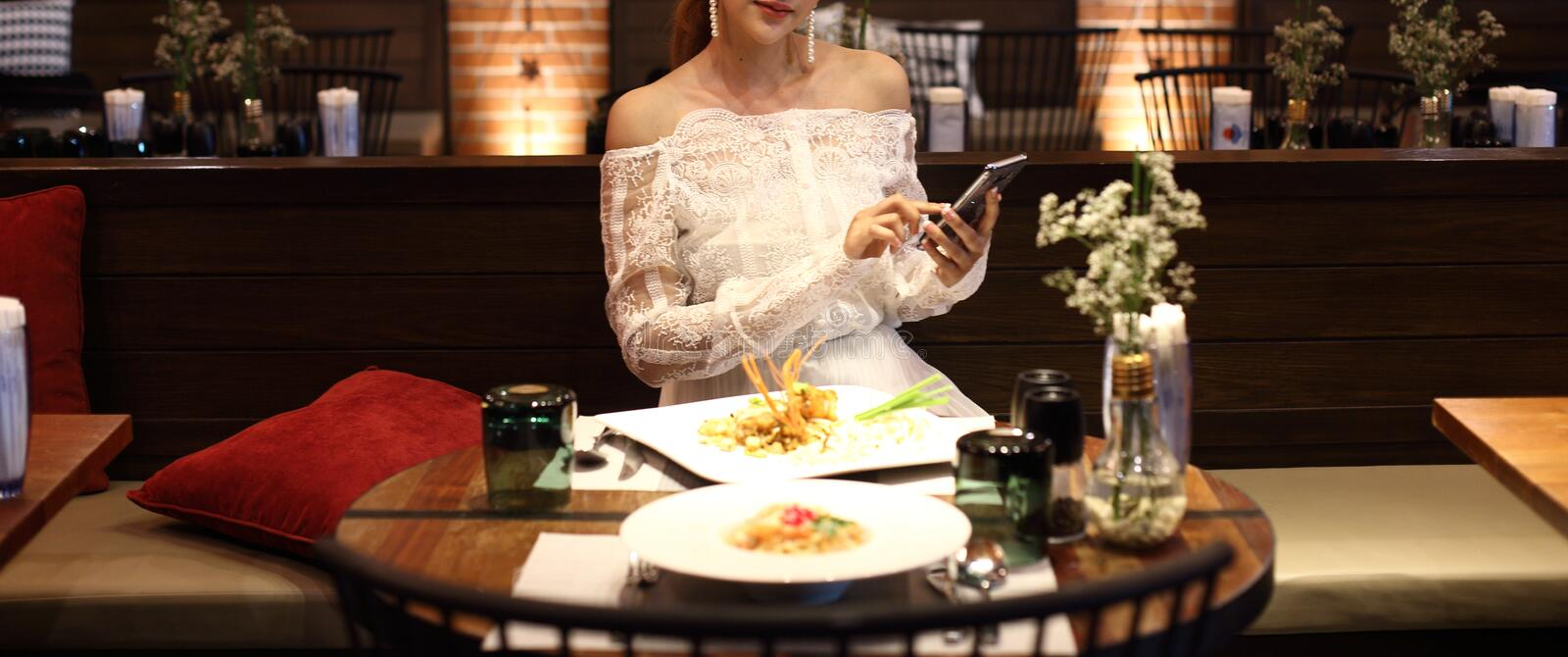 Woman white lace dress have dinner in restaurant. With low light candle waiting for lover to join celebrate anniversary night together but come so late and feel royalty free stock image