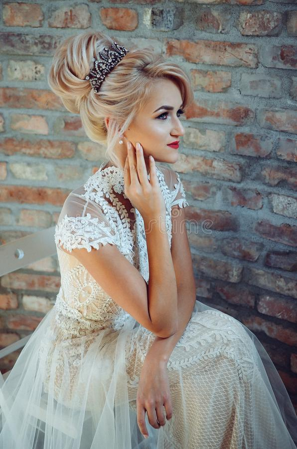 Woman in White Lace Dress Sits on Chair stock photos