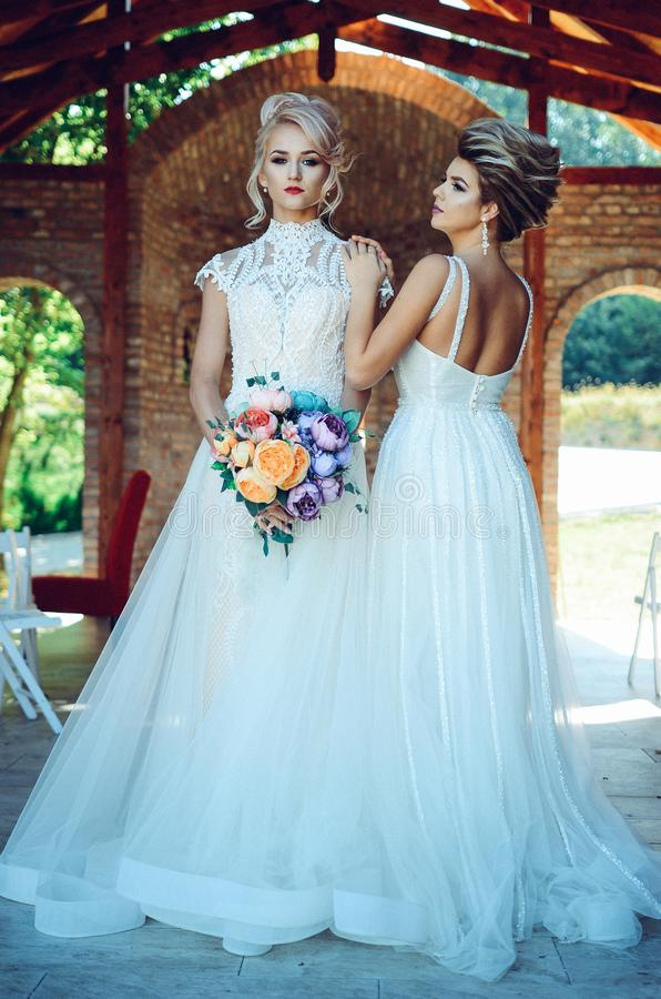 Woman in White Lace Wedding Dress Holding Flower Bouquet Beside Woman in White Dress stock photos