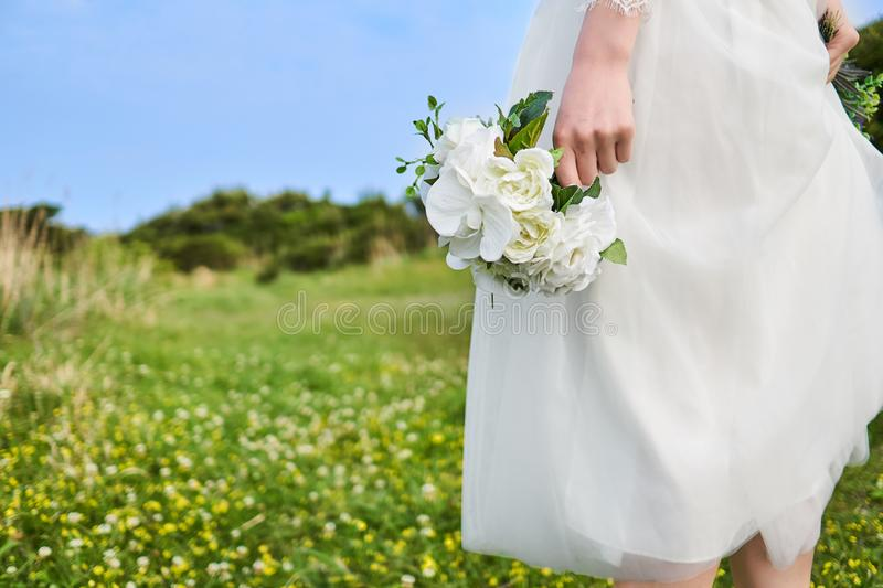 Woman in white laced bridal dress holding white bouquet at her side at the yellow blossom field located on a cliff royalty free stock image