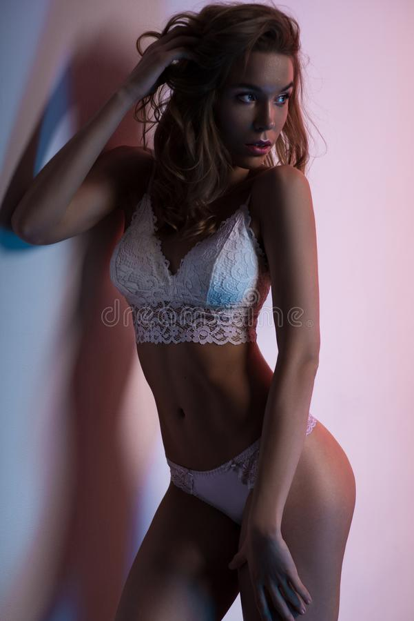 Woman in white lingerie posing in studio royalty free stock photography