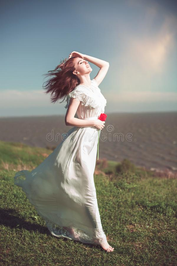 woman in white long fluttering dress on the sea coast stock photography