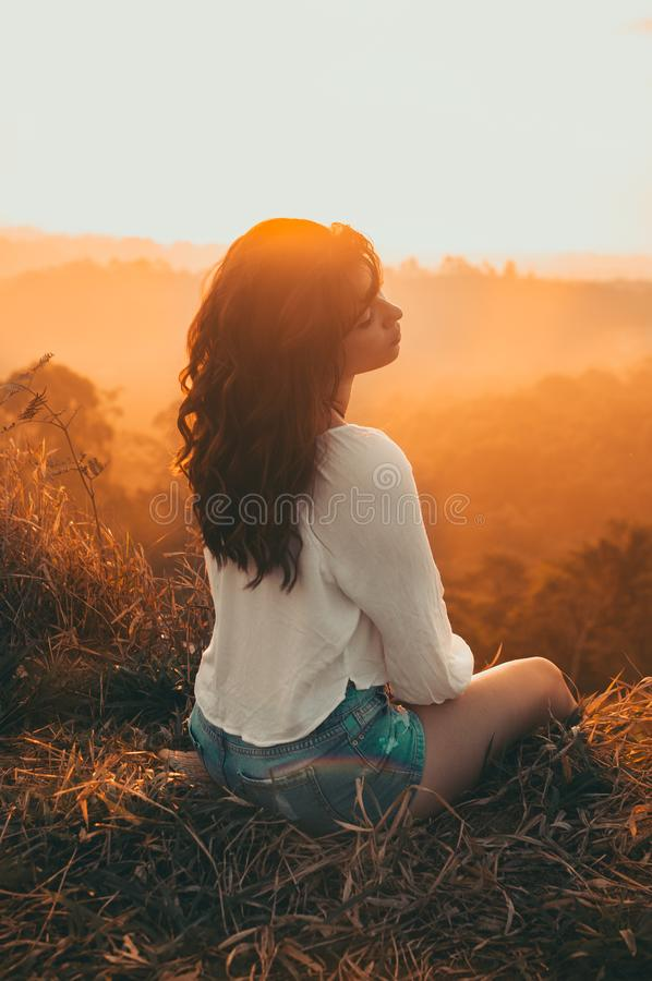 Woman in White Long-sleeved Shirt With Blue Short Shorts Sitting on Brown Grass Against Golden Hour Light stock photo