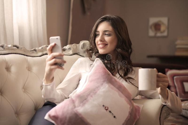 Woman in White Long-sleeved Shirt Holding Smartphone Sitting on Tufted Sofa stock photo